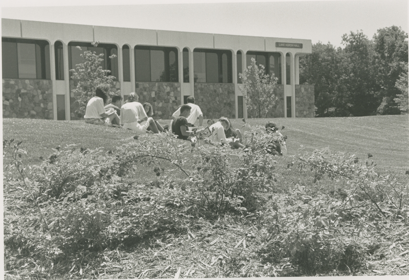 Go to Lake Huron Hall. Group of students sitting outside item page