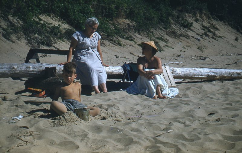 Go to Two women and a child reclining against log on the beach item page