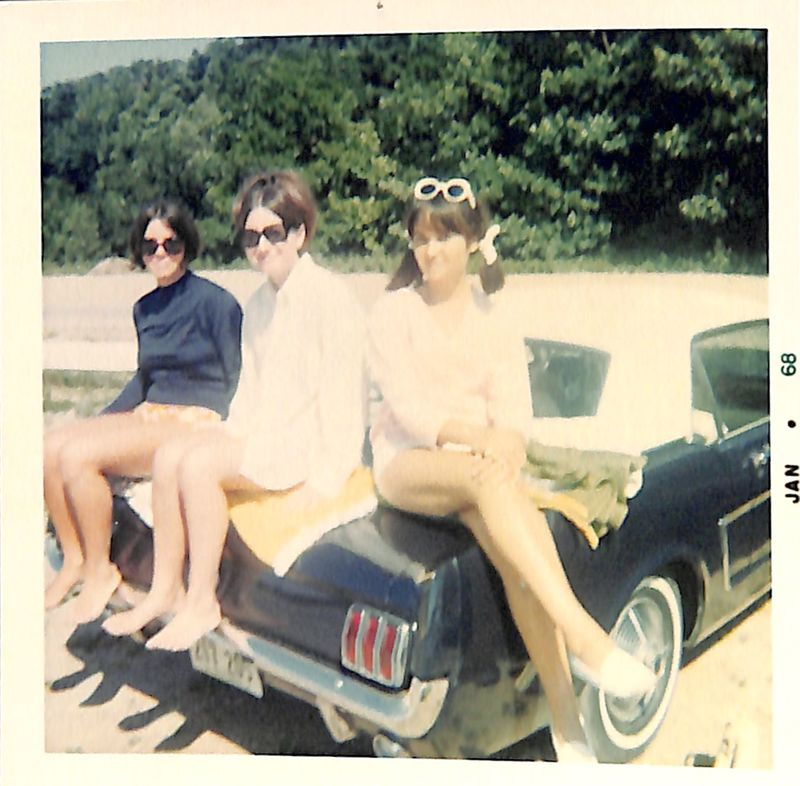 Go to Three young women sitting on a car at the beach item page