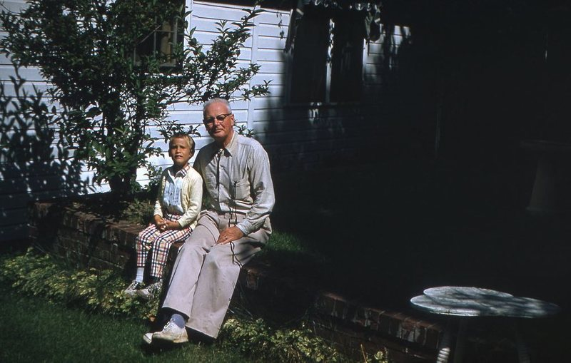 Go to Young boy and elderly man sitting in the yard item page