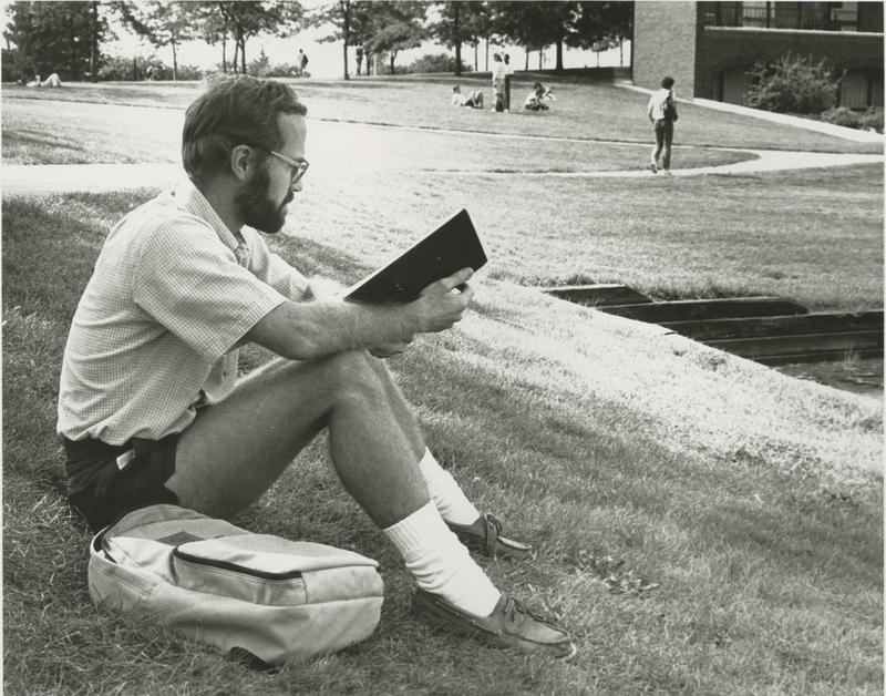Go to Zumberge Pond. Man reading near Zumberge Pond item page