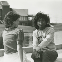Go to Zumberge Pond. Two female students sitting outside item page