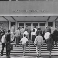Go to Lake Superior Hall. Students in beanies walking up the steps item page