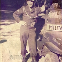 "Go to Edward ""Ned"" Manley in Military Police uniform leaning against a jeep, circa 1945 item page"