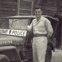 "Go to Edward ""Ned"" Manley leaning on Military Police jeep, circa 1945 item page"